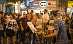 Jerusalem, Israel - July 20, 2013: Late on a Saturday night, after Shabbat, a man sings and plays guitar before a small audience on Ben Yehuda Street in Jerusalem.