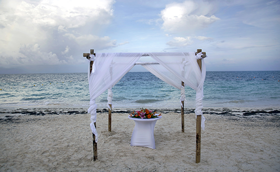A beach canopy set up for a wedding with flowers on a table and the ocean in the background. Shot just before sunset with a Canon 5D MarkII with a polarizer filter.