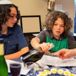 Brothers are sitting at a dinning room table participating in a Passover seder.  rm