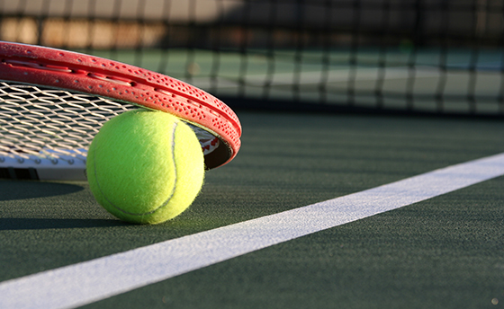 Tennis racket lying on a tennis ball near the net and court line
