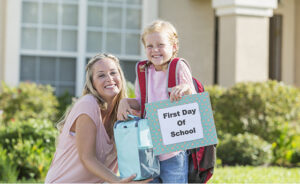 A little girl standing outside her home with her mother carrying a bookbag and lunchbox.  She is eager and ready to go back to school, holding up to sign that says FIRST DAY OF SCHOOL.