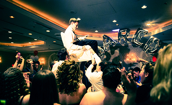 Bar Mitzvah celebration. Brother of the Bar Mitzvah boy is held up on a chair. It is traditional for the child and his family to be raised on chairs during the party.