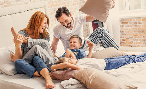 Our happy family. joyful parents spending time with their smiling children while playing with pillows in bed