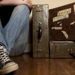 Floor level perspective of a young man wearing jeans, tennis shoes and a black tshirt sitting and leaning against a wall next to three old suitcases. Concept for travel or leaving for college.