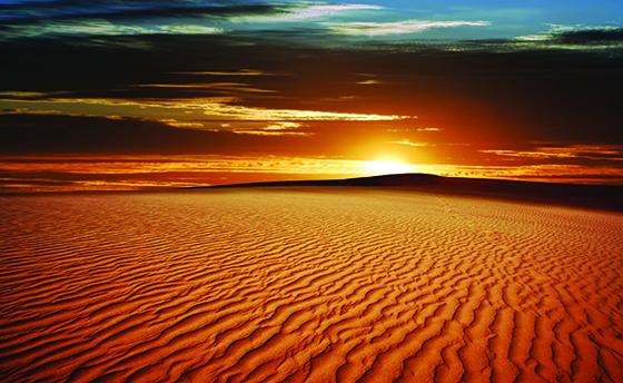 rippled desert sand dunes at sunset