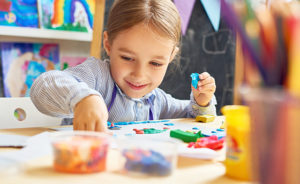 Portrait of smiling little girl working with plasticine in art and craft class of development school