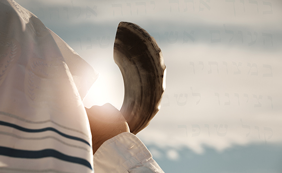Jewish man blowing the Shofar with hebrew words from the prayer book in the background