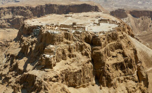Aerial View of Masada Israel shot from a helicopter. Masada is an ancient fortification in the Southern District of Israel situated on top of an isolated rock plateau akin to a mesa on the eastern edge of the Judaean Desert, overlooking the Dead Sea. Herod the Great built palaces for himself on the mountain and fortified Masada between 37 and 31 BCE. According to Josephus, the Siege of Masada by troops of the Roman Empire towards the end of the First Jewish–Roman War ended in the mass suicide of the 960 Sicarii rebels and their families hiding there.