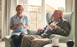 Indoor shot of smiling senior man and female carer enjoying coffee in living room