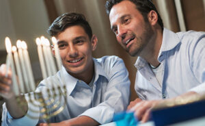 A father and his teenage son celebrating hanukkah, lighting the menorah.