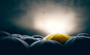 Unique and different yellow umbrella standing out of the crowd from black ones in a dramatic scene