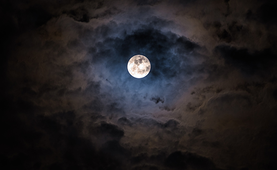Mysterious dark night sky with full moon and clouds