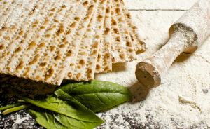 traditional Jewish kosher matzo for Easter pesah on a wooden table. Jewish Easter food. Spring. Flour and rolling pin. Preparation of matzo
