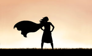 Strong Beautiful Caped Super Hero Woman Silhouette Isolated Against Sunset Sky Background