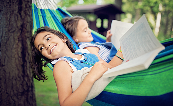 Two girls are lying down in the hammock and reading books