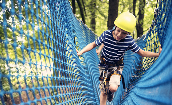 Little boy wearing a helmet walking through difficult obstacle in ropes course in adventure park. The laughing boy is crossing a net.