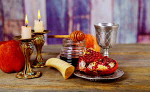 Honey, apple and pomegranate on wooden table shofar, honey and pomegranate over bokeh background