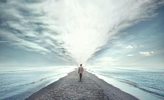 man walking between two seas