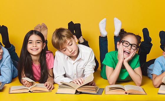 Children lying on floor and reading books