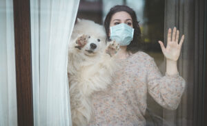 Young woman wearing medical mask, standing near the window with dog