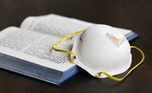 N95 Mask and hebrew prayerbook: pray indoors concept.