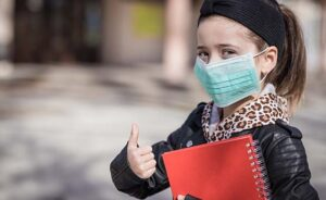 Girl with a book and protective mask pointing thumb up