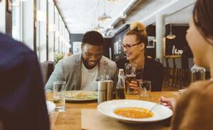 Multi ethnic group of friends eating dinner in a restaurant